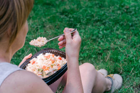 Anonymous woman eating homemade food prepared in a reusable plastic lunch box in the field. Summer vacation, eating outdoors.