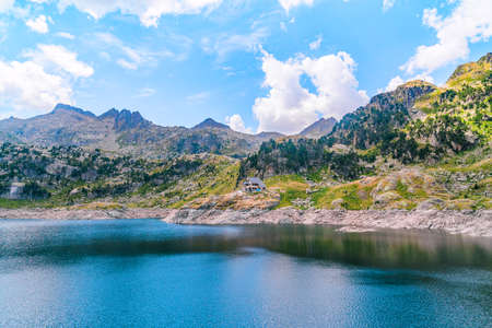 Mountainous landscape with a beautiful blue lake and a mountain refuge in a green alpine valley on a sunny summer day. Concept of summer vacations and mountain trip.