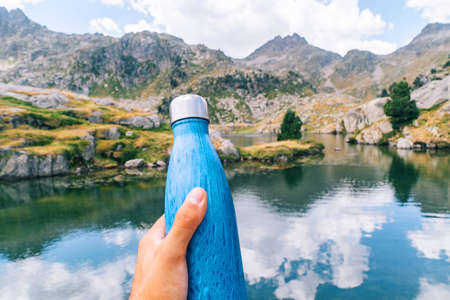 Selective focus on a blue water bottle in a person's hand with an alpine mountain landscape in the background 免版税图像