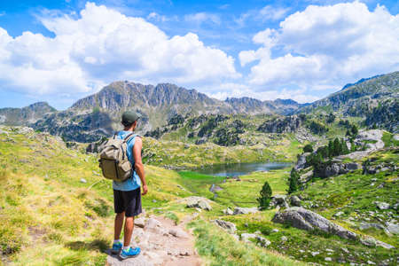 Young man with a bag standing on an alpine mountain trail with a lake.