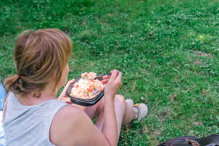 Woman eating homemade food prepared in a reusable plastic lunch box in the field. Summer vacation, eating outdoors.