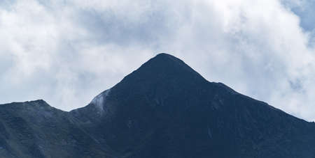 Panoramic view of a peak of a high mountain on a cloudy day. Mountain range. Mountaineering and nature concept.