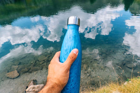 Hand holding a plastic free reusable blue water bottle. Concept of mountains, nature, climate change and ecological bases.