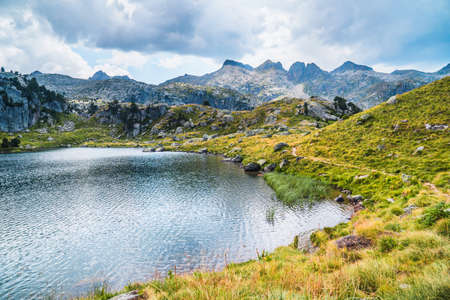 Mountain lake surrounded by mountains. Concept of mountain trip and summer vacations. Circo Saboredo, Aran Valley-Pyrenees, Catalonia, Spain.