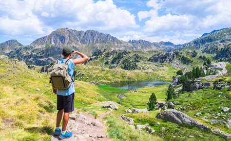 Young traveler man with a backpacker standing on an alpine mountain trail with a lake. Circo de Saboredo, Aran Valley, Catalan Pyrenees, Catalonia, Spain, Europe.