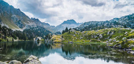 Landscape of mountain lake surrounded by mountains reflected in the water. Concept of mountain trip, summer vacations and nature. Circo Saboredo, Aran Valley-Pyrenees, Catalonia, Spain. 免版税图像