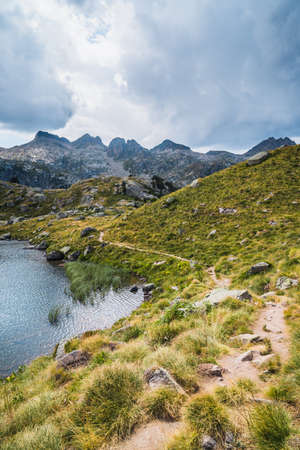 Mountain landscape with hiking trail and mountain lake surrounded by alpine mountains. Concept of mountain trip and summer vacations. Circo Saboredo, Aran Valley-Pyrenees, Catalonia, Spain.