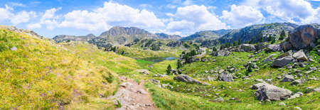 Panoramic view of mountainous landscape with beautiful green mountains and a lake on a sunny day. Concept of mountain trip and summer vacations. Circo Saboredo, Aran Valley-Pyrenees, Catalonia, Spain.