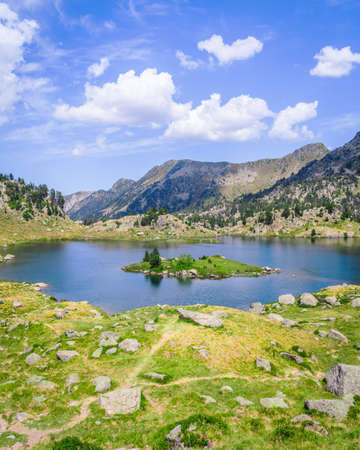 Beautiful Mountain lake surrounded by mountains with green grass on a lovely sunny summer day. Concept of mountain trip and summer vacations. Circo Saboredo, Aran Valley-Pyrenees, Catalonia, Spain. 免版税图像