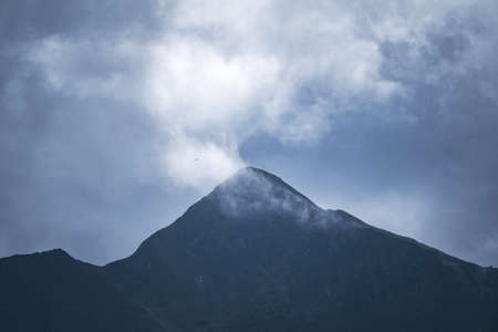 Peak of a high mountain on a cloudy and foggy day. Mountain range. Mountaineering and nature concept. 免版税图像