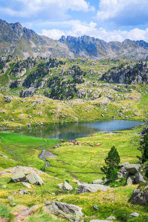 Mountainous landscape with beautiful green mountains and a lake on a sunny day. Concept of mountain trip and summer vacations. Circo Saboredo, Aran Valley-Pyrenees, Catalonia, Spain.
