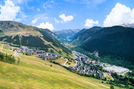 Aerial view of Baqueira Beret town in the Vall de Aran surrounded by beautiful green mountains on a sunny summer day. Summer tourism in Aran Valley, Pyrenees, Catalonia, Spain. 免版税图像
