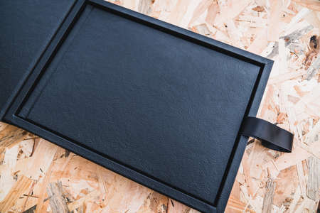 Black leather photo album on a table with vintage wood background. Wedding or family photo book memories with a nice leather box. Family value memory.