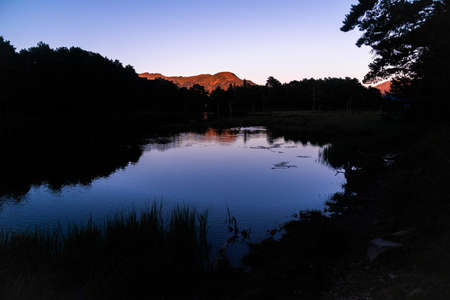 Beautiful sunrise or sunset on an alpine lake in the Pyrenees, Catalonia, Spain. Concept of vacations, summer, relaxation and disconnection in nature. Wilderness.