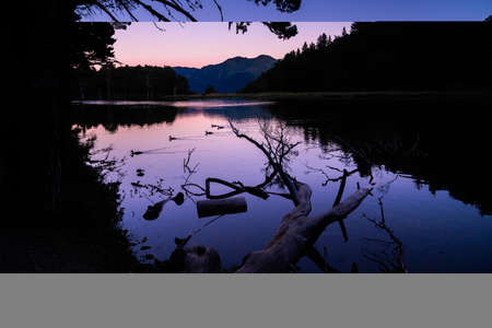 Fantastic evening panorama of alpine mountain lake. Picturesque sunset or sunrise of beautiful landscape with illuminated peaks, silhouette of some ducks and trees. Beauty of nature concept.