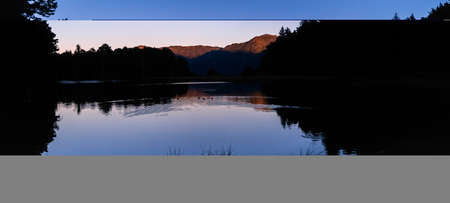 Panoramic landscape of beautiful sunrise or sunset on an alpine lake in the Pyrenees, Catalonia, Spain. Concept of vacations, summer, relaxation and disconnection in nature. Wilderness. 免版税图像