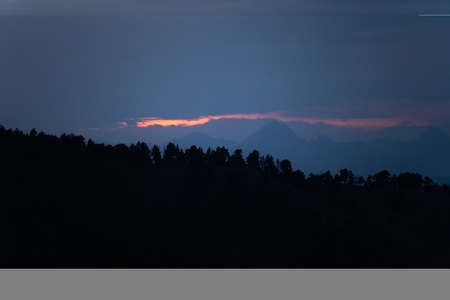 Landscape with dark misty silhouettes of alpine mountains and fir trees forest in Pyrenees.