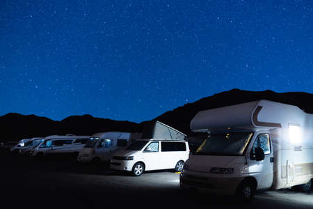 Campers parked in a caravan parking area sleeping on a starry night in the mountain. Summer tourism with RV in a blue night sky with stars. Best option for travel. Motorhomes and camping car. 免版税图像