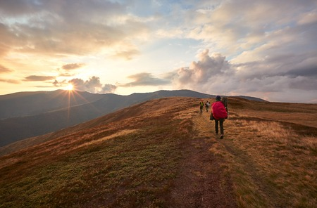 Two hikers with backpack walking along the trail on the mountain top at sunset time. Travel lifestyle concept. Ukraine, Borzhava