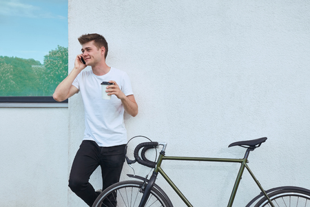 Young hipster style man posing with bicycle on the street sport style picture handsome guy white wall
