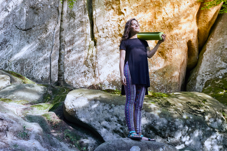 Young attractive girl stand on the big rock in forest and holding a yoga mat and a cup. Preparing for practicing yoga on a yoga mat. Stock Photo