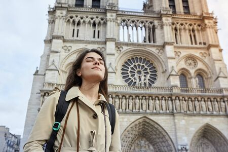 Young smiling woman tourist standing in front of the famous Notre Dame cathedral in Paris