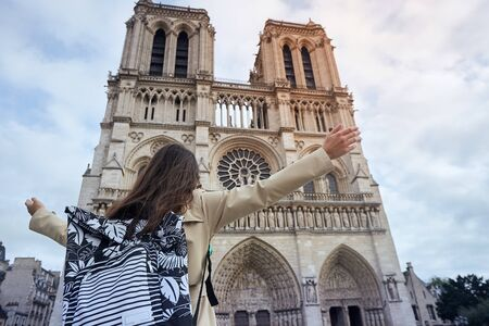 Young happy woman standing in front of the famous Notre Dame cathedral in Paris, hands raised up to the sky