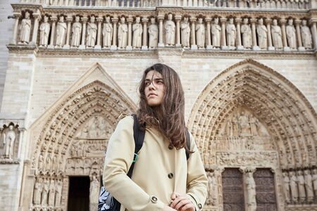 Young sensitive woman tourist standing in front of the famous Notre Dame cathedral in Paris 写真素材