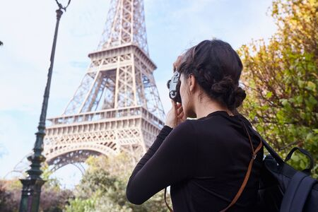 Beautiful girl posing with a camera taking pictures of the Eiffel Tower. Paris, Champ de Mars