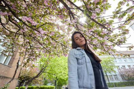 Young smiling woman posing on the background of blooming sakura