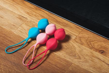Multi-colored vaginal balls. Color Kegel balls, Geisha balls on wodden background. Sex toys. Place for text. Sex shop concept. Copy space. Adult store.