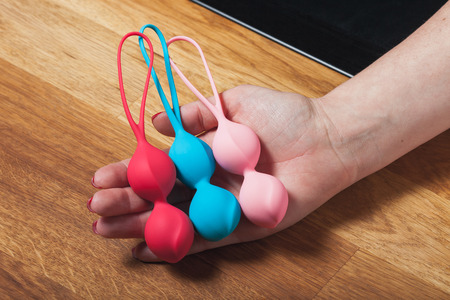 Female hand holding toys. Color Kegel balls, Geisha balls on wodden background. Multi-colored vaginal balls in a woman hand. Sex toys. Place for text. Sex shop concept. Copy space. Adult store.