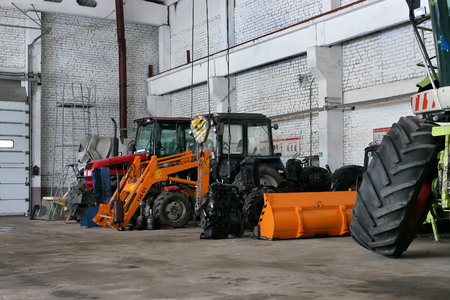 the agricultural tractors in the shop preparing for planting