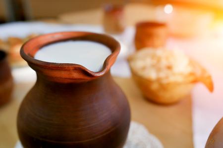 clay jug of milk on the table . Organic food