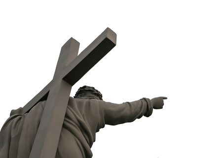 statue of Jesus with a cross on his back shows the way Stock Photo