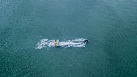 Inflatable banana boat with tourists in blue calm sea. Group of people riding banana boat. Speeding away.