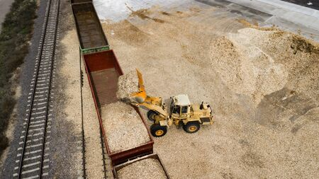 the loader loads the sawdust in the woodworking factory aerial view Standard-Bild