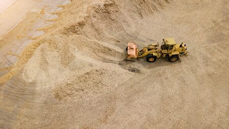 the loader loads the sawdust in the woodworking factory aerial view