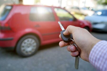 key in hand on blurred car background