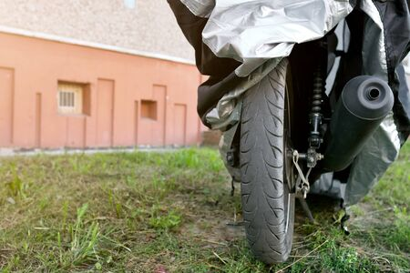 motorcycle under protective cover on the street