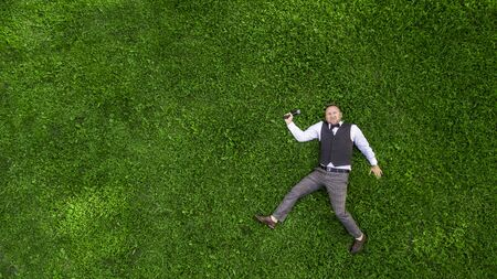 happy presenter with a microphone on the green lawn view from above aerial photography with drone