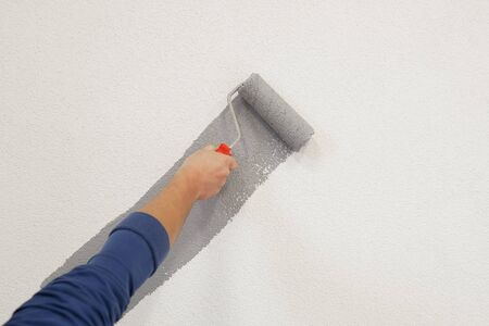 hand with paint roller in hand, painting a wall