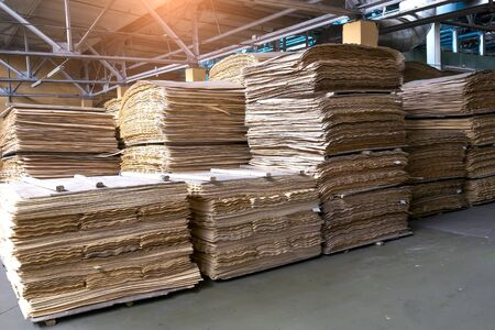 Stacked plywood and wooden board products against de-focused blurred piece of industrial warehouse storage on production site. Copy space. Selective focus.