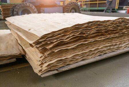 Gestapelte Sperrholz- und Holzplattenprodukte gegen unscharfes, unscharfes Stück Industrielager am Produktionsstandort. Platz kopieren. Selektiver Fokus. Standard-Bild