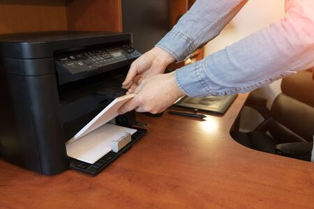 Human hand is reloading the paper to printer tray Banque d'images