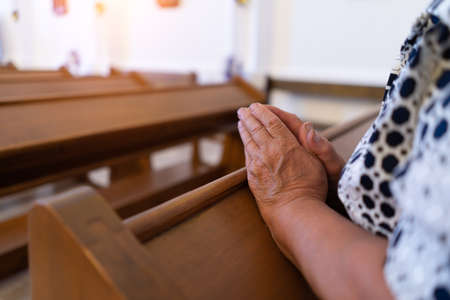 elderly woman praying in church with folded arms close up. Foto de archivo