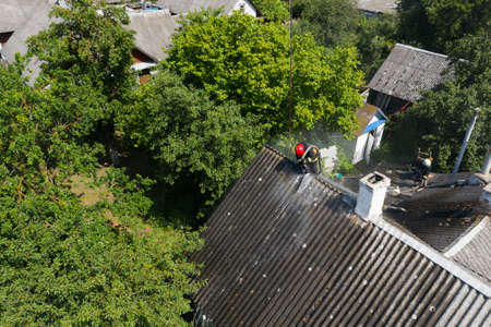 firefighter on the roof extinguishes the fire view from above.