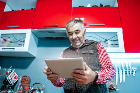 an elderly man with a tablet in his hands.