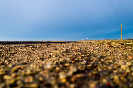 a road stretching into the distance against a blue sky.