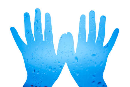 water drops on the glass on the hands on a white background. 免版税图像